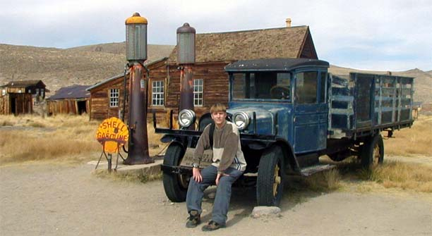 Scott Zeise, looking a bit like Jim-boy Walton, rests on the bumper of a 30's-era truck abandoned at the Bodie, CA, gas station.
